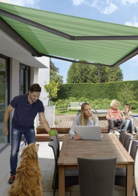 Glückliche Familie verbringt Zeit auf der Terrasse mit ausgefahrener Markise